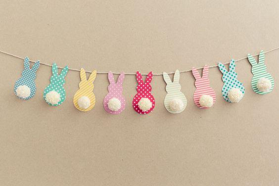 ghirlanda di conigli di carta con pom pom per decorare la tavola di pasqua